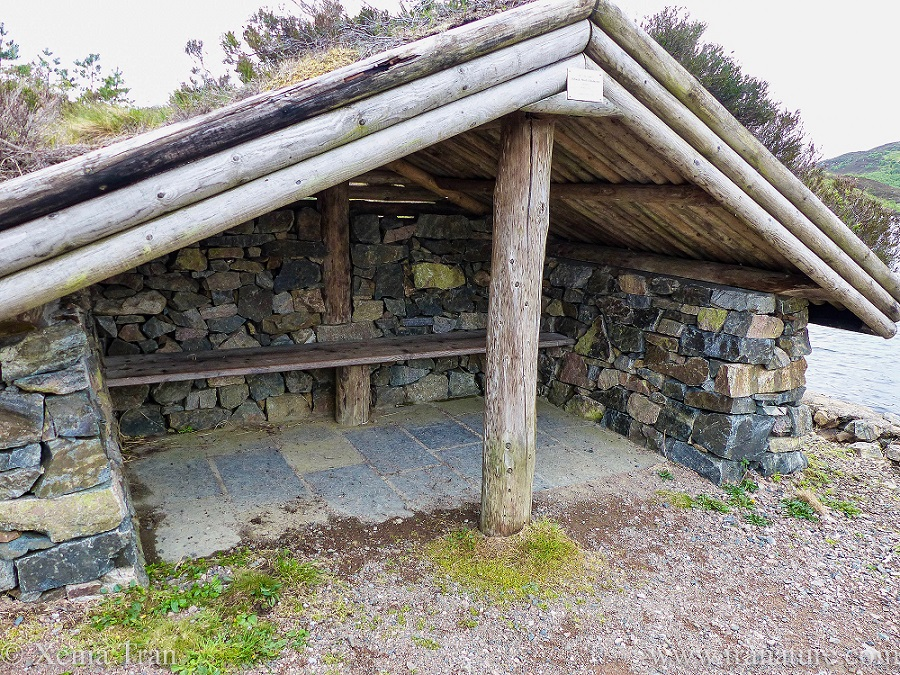 stone and wood shelter with a grass roof by Loch Leitir Easaidh
