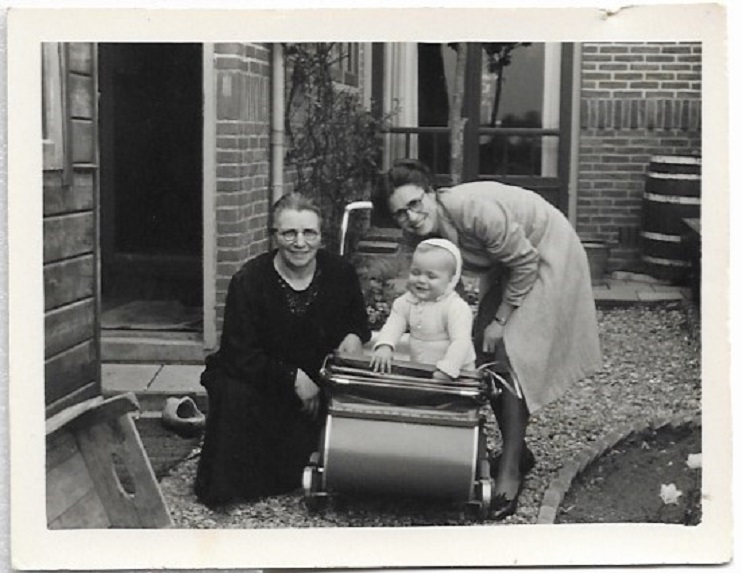 a black and white family photograph featuring two women and a baby boy in a pram