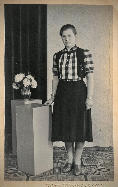 a black and white old photograph of a woman standing next to pillars with a vase of flowers