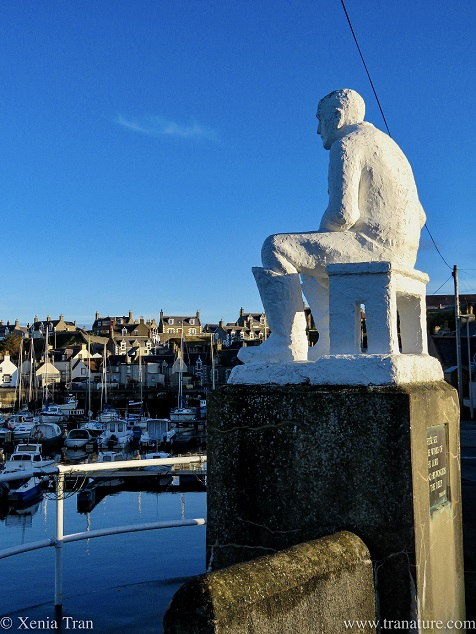 white sculpture of a seated fisherman overlooking Findochty harbour