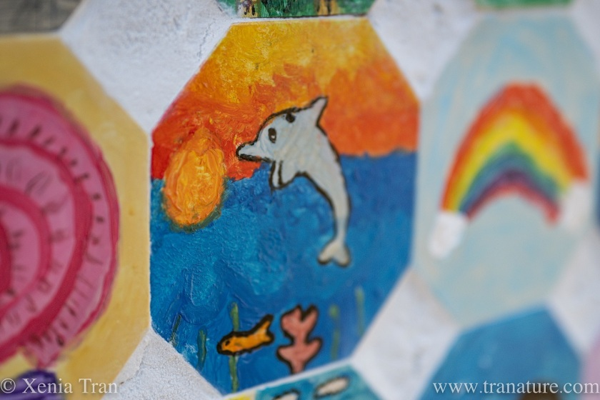 a hand-painted wall tile with a leaping dolphin at sunset